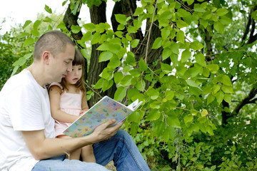 Отец и дочка читают книгу на природе