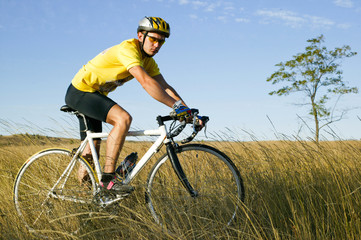 Юноша велосипедист в желтой форме на природе