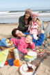 Family Having Picnic On Winter Beach