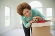 Hispanic woman opening box to find pet dog