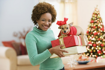 Hispanic woman carrying Christmas presents and pet dog
