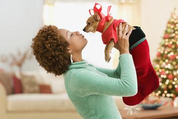 Hispanic woman kissing pet dog in costume