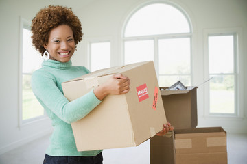 Hispanic woman moving boxes into new home