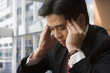Chinese businessman rubbing forehead