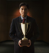 Chinese businessman holding trophy