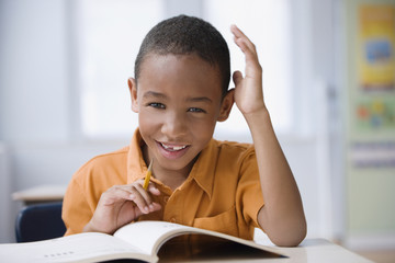 Grinning African boy studying in classroom