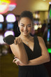 Glamorous mixed race woman in casino holding purse