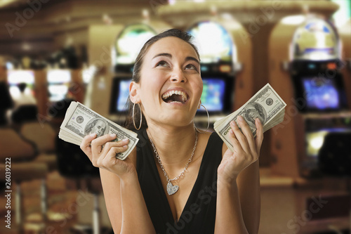 Glamorous mixed race woman in casino holding 100 dollar bills