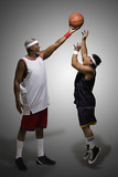 Tall basketball player keeping ball from shorter player