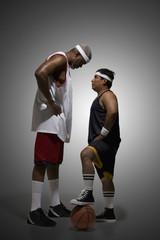 Tall basketball player looking down at shorter player