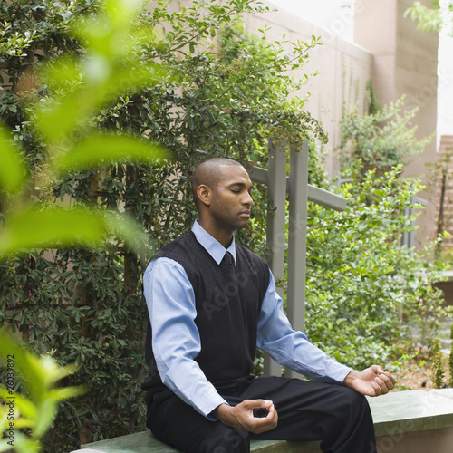 African businessman meditating in garden