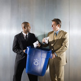 Businessmen holding recycling bin