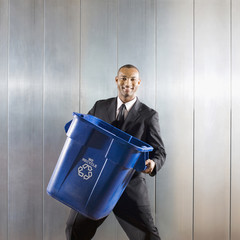 African businessman carrying recycling bin