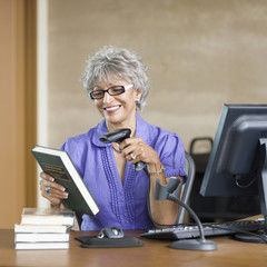Hispanic librarian checking in books in library