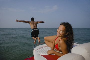 Man jumping off boat as girlfriend watches