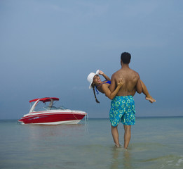 Man wading in ocean and carrying girlfriend