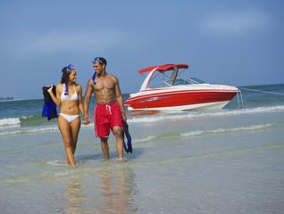 Couple wading in ocean with snorkel gear near boat