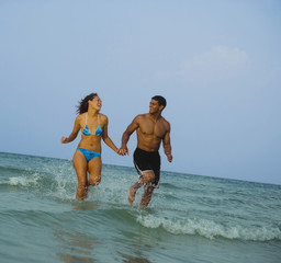 Couple holding hands and running in ocean