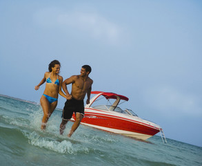 Couple holding hands and running in ocean near boat