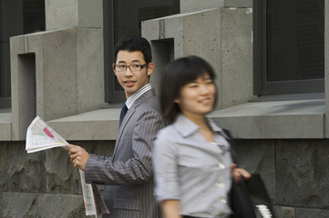 Korean businessman with newspaper watching woman walking