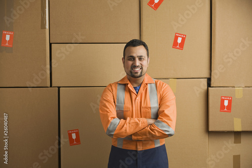 Indian worker standing near cardboard boxes