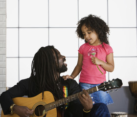 """African father playing guitar, daughter singing"""