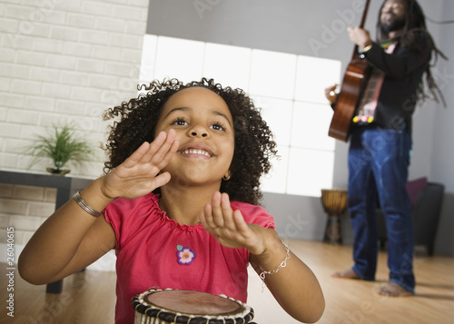 African father and daughter playing musical instruments