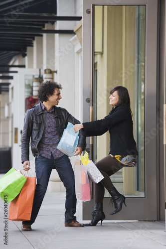 Woman pulling boyfriend into store