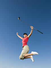 Native American woman with golf club jumping in mid-air