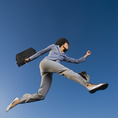 African businesswoman carrying briefcase in mid-air