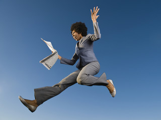 African businesswoman reading newspaper in mid-air