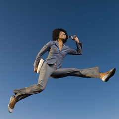 African businesswoman talking on cell phone in mid-air