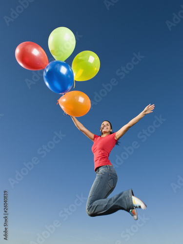 Native American holding balloons in mid-air