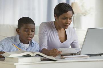 African boy doing homework next mother on computer