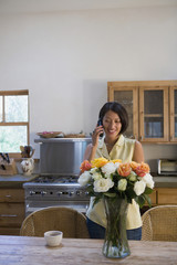 Native American talking on cell phone in kitchen