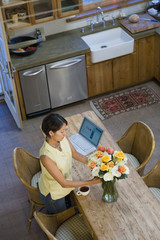 Native American arranging flowers in kitchen