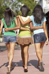 Teenage friends hugging and walking