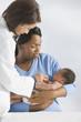 Doctor listening to African newbornÕs heartbeat