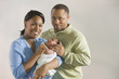 African couple standing with newborn baby