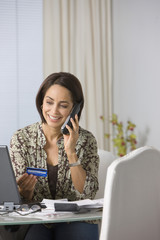 Hispanic woman paying bills by telephone with credit card