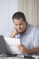 Frustrated Hispanic man paying bills