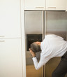 Hispanic businessman looking into ice maker on refrigerator
