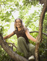 Low angle view of Hispanic girl in tree