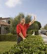 Middle-aged Hispanic man waving next to hedge