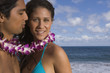 Portrait of couple wearing lei at beach