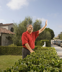 Middle-aged Hispanic man waving next to hedge