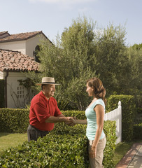 Hispanic man and woman shaking hands over hedge