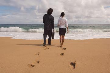 Businessman and businesswoman walking towards ocean