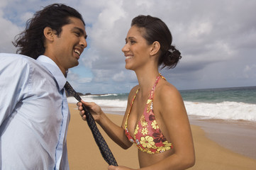 Woman pulling man's necktie at beach