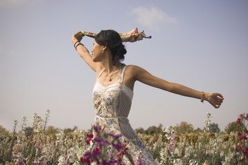 Asian woman with arms outstretched in meadow